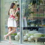 Young beautiful brunette woman in white flowers dress walking on Royalty Free Stock Photography