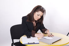 Young beautiful business woman. Taking notes at the office Stock Photo