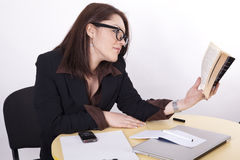 Young beautiful business woman. Bored in the office reading a book Royalty Free Stock Image