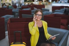 Young beautiful business woman in the airport lounge uses a smartphone and tablet. stock image