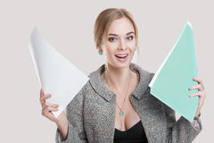Young beautiful business woman in black dress, jacket holding folder of papers and smiling on gray background Stock Images