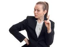 Young beautiful business woman in black jacket keeps her hand on the side shows the gesture and looks into a camera Royalty Free Stock Image