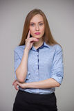 Young beautiful business woman in a blue shirt stands with her a Stock Photos