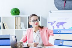 Successful business woman at modern office. Young beautiful business woman boss  in glasses is working focused with documents at her workplace. Girl employee stock photo