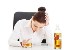 Young beautiful business woman with glass of whisky or rum. Stock Photos