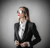 Young beautiful business woman with glasses. Young beautiful business woman wearing glasses and a white shirt and a black jacket Royalty Free Stock Image
