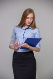 Young beautiful business woman is holding a document tablet and pen and is thinking on a gray background Royalty Free Stock Photo