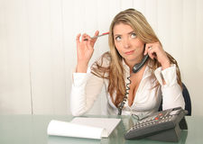 Young beautiful business woman, holding phone and thinking. Young beautiful business woman, in office holding phone and thinking Royalty Free Stock Images