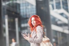Young beautiful business woman holding tablet, working in downtown, outdoors Stock Photo