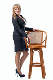 Young beautiful business woman inviting to sit on a chair. White isolated background royalty free stock photo
