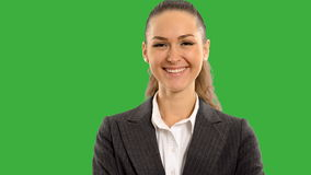 Young beautiful business woman looking at the screen smiling with crossed arms  on a green background with alpha channel. close up stock video footage