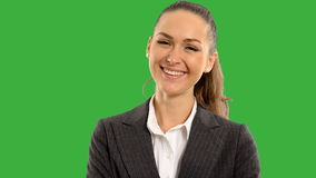 Young beautiful business woman looking at the screen smiling with crossed arms  on a green background with alpha channel. close up stock footage
