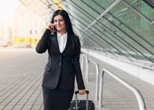 Young business woman with mobile phone and suitcase in urban setting. Young beautiful business woman with mobile phone and suitcase in urban setting Stock Photography