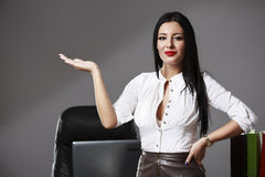 Young beautiful business woman pointing at copyspace. A young beautiful business woman pointing at copyspace Royalty Free Stock Photos