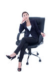 Young beautiful business woman sitting on the chair and dreaming. Isolated on white background Royalty Free Stock Images