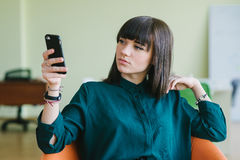 Young beautiful business woman sitting in a modern office on a chair and use the phone. Break work. Young beautiful business woman sitting in a modern office on Stock Images