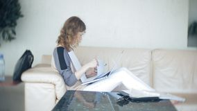 Young beautiful business woman sitting on sofa at table with tablet and looking through paper. 4k stock footage