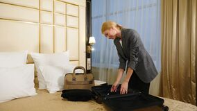 Young beautiful business woman unpacking suitcase in hotel room. Travel and hotel concept. Woman traveler in light. Luxury hotel room. 4k stock video