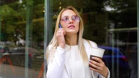 Young beautiful business woman using cell phone and holding coffee cup outside. In slow motion. young caucasian female negotiating with partner on smartphone stock footage