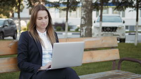Young Beautiful Business Woman Using Laptop PC Sitting On Bench Outdoors