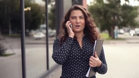 Young beautiful business woman walks next to an office building with documents and talks on the phone while distracted. Close-up. Young beautiful business woman stock video