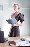 Young beautiful business woman at work with book Stock Images