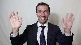 Young beautiful businessman in blue suit smiling and waving her hand greeting customers. Portrait on a white background stock video