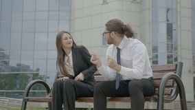 Businesswoman and businessman sitting on a bench in front the corporation looking in the eyes bumping fists and dancing -. Young beautiful businesswoman and stock video