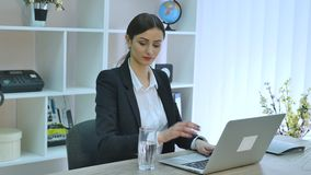 Young beautiful businesswoman drinking water at work.  stock video footage