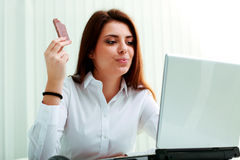 Young beautiful businesswoman eating chocolate at her workplace Royalty Free Stock Photos
