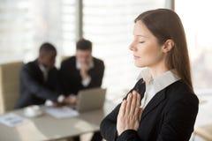 Young beautiful businesswoman enjoys meditating in office with e. Young beautiful businesswoman enjoys meditating standing in office with eyes closed, put hands Stock Photos