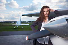 Young beautiful businesswoman in front of airplane. Royalty Free Stock Images