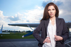 Young beautiful businesswoman in front of airplane. Royalty Free Stock Photos