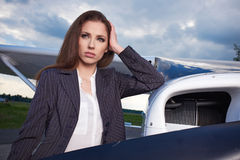 Young beautiful businesswoman in front of airplane. Royalty Free Stock Photo