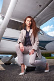 Young beautiful businesswoman in front of airplane. Stock Image