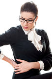 Young beautiful businesswoman having back pain Stock Images