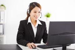 Young beautiful  businesswoman with headset in office Royalty Free Stock Photography
