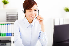 Young beautiful businesswoman with headset in office Stock Photos