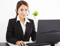 Young beautiful businesswoman with headset in office Stock Image
