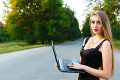 Young beautiful businesswoman holding laptop on the road Royalty Free Stock Image