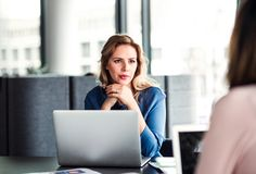 Young businesswoman with laptop sitting in an office, talking to a colleague. Young beautiful businesswoman with laptop sitting in an office, talking to a stock photo