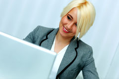 Young beautiful businesswoman looking at laptop display Royalty Free Stock Images
