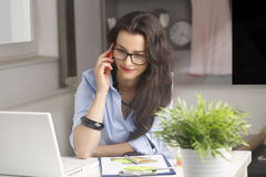 Young beautiful businesswoman making a phone  and working at hom Stock Image