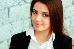 Young beautiful businesswoman near brick wall Stock Photo