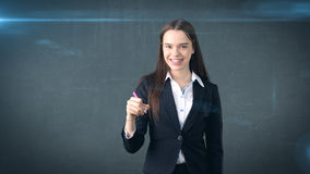 Young beautiful businesswoman with pen writing on the screen. Royalty Free Stock Photo