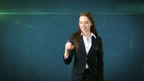 Young beautiful businesswoman with pen writing on the screen. Stock Photos