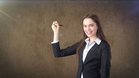 Young beautiful businesswoman with pen writing on the screen. Royalty Free Stock Photos