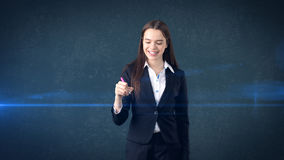 Young beautiful businesswoman with pen writing on the screen. Young longhair beautiful businesswoman with pen writing on the screen royalty free stock photo