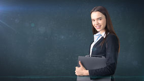 Young beautiful businesswoman portrait with gray briefcase, dark background Stock Photos