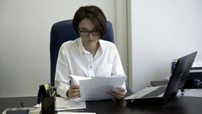 Young and beautiful businesswoman with short, dark hair in white shirt is tired from work in the office. Young office stock photography